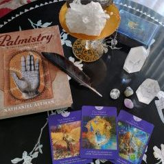 Three tarot cards on a black table with a black feather, crystals, and Palmistry book.